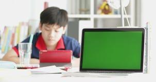 Glücklicher asiatischer Junge, der auf Tablet-Computer mit Lächeln aufpasst, zu Hause gegenüberzustellen stock video footage