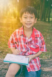 Glücklicher asiatischer Junge, der ein Buch lächelt und hält getrennte alte Bücher V Stockbild