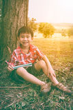 Glücklicher asiatischer Junge, der ein Buch lächelt und hält getrennte alte Bücher V Lizenzfreies Stockbild