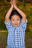 Glücklicher asiatischer Junge, der mit Herbst-Blättern spielt Lizenzfreie Stockfotografie