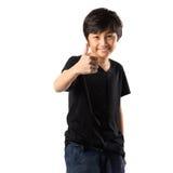 Glücklicher asiatischer Junge, der sich Daumen zeigt stockbild