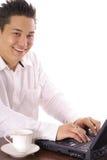 Glücklicher asiatischer Mann, der an Computer arbeitet Stockbild