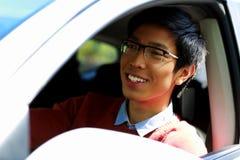 Glücklicher asiatischer Mann, der im Auto sitzt Stockbild