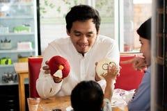 Gl?cklicher asiatischer Vater und sein todler, die zusammen Zeit nach innen am Kuchenspeicher und -caf? verbringt stockbild