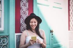 Glücklicher Asien-Mode Blogger, der den Handy im Freien - chinesisches Mädchen hat Spaß mit neuen Tendenzen Smartphone Apps verwe stockfoto