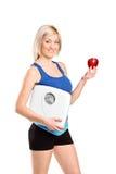 Glücklicher Athlet, der eine Gewichtskala anhält Lizenzfreies Stockbild