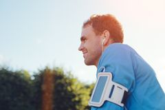 Glücklicher Athlet mit hörender Musik der Armbinde im Park Stockfoto