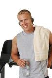 Glücklicher athletischer Mann, der an einer Tretmühle sich lehnt Lizenzfreies Stockfoto