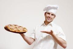 Glücklicher attraktiver Koch mit einer Pizza in den Händen Stockfotografie
