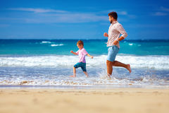 Glücklicher aufgeregte Vater und der Sohn, die auf Sommer läuft, setzen auf den Strand, genießen das Leben stockbilder