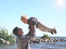 Glücklicher aufgeregte Vater und der Sohn, die auf Sommer spielt, setzen auf den Strand, genießen das Leben lizenzfreies stockfoto