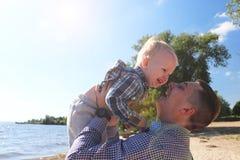 Glücklicher aufgeregte Vater und der Sohn, die auf Sommer spielt, setzen auf den Strand, genießen das Leben lizenzfreie stockfotografie