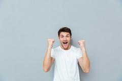 Glücklicher aufgeregter junger Mann, der Erfolg schreit und feiert lizenzfreie stockbilder