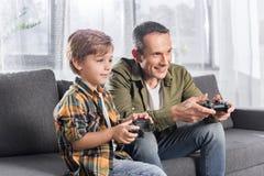 glücklicher aufgeregter Vater und Sohn, die Konsole mit gamepads beim Sitzen spielt stockbild