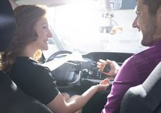 Glücklicher Autohändler, der lächelnder Frau Schlüssel während der Probefahrt gibt lizenzfreie stockbilder
