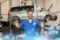 Glücklicher Automechanikermann oder -Schmied an der Autowerkstatt Lizenzfreie Stockfotos