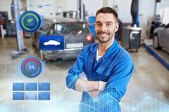 Glücklicher Automechanikermann oder -Schmied an der Autowerkstatt Stockfotografie