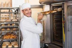 Glücklicher Bäcker, der frische Bagel herausnimmt Lizenzfreie Stockfotos