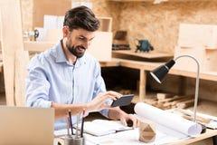 Glücklicher bärtiger Bauholzhandwerker, der modernes Gerät in seiner Arbeit verwendet Stockbilder