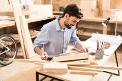 Glücklicher bärtiger hölzerner Meister, der mit Bauholzstreifen in der Werkstatt arbeitet Lizenzfreies Stockbild