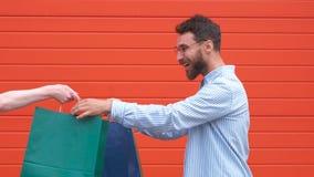 Glücklicher bärtiger Kerl des Porträts mit Gläsern nimmt die Taschen in seinen Händen Einkauf im Speicher stock video footage