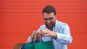 Glücklicher bärtiger Kerl des Porträts mit Gläsern nimmt die Taschen in seinen Händen Einkauf im Speicher stock footage
