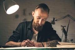 Glücklicher bärtiger Mann, der bei Tisch Bilder schafft Lizenzfreie Stockfotos