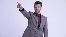 Gl?cklicher b?rtiger persischer Gesch?ftsmann, der Finger verweist und zeigt stock video footage