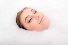 Glücklicher Badekurort: schönes attraktives junge Frau Brunettemädchen, das Spaß im Schaum genießt die Augen geschlossen, Nahaufn Stockfotografie