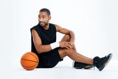 Glücklicher Basketball-Spieler des jungen Mannes, der weg sitzt und schaut lizenzfreies stockbild