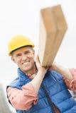 Glücklicher Bauarbeiter Carrying Wooden Plank Lizenzfreies Stockfoto
