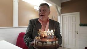 Glücklicher beachtlicher Holdingkuchen des alten Mannes Feiern des Geburtstagsjahrestages stock footage