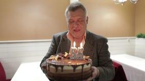 Glücklicher beachtlicher Holdingkuchen des alten Mannes feiern Schlaggeburtstagskerzen stock footage