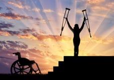 Glücklicher Behinderter, der auf Treppe steht und Krückenrollstuhl hält Stockbild