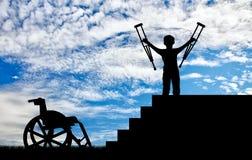 Glücklicher behinderter Junge, der auf sters mit Krücken in seinen Händen und in Rollstuhl steht Lizenzfreie Stockfotografie