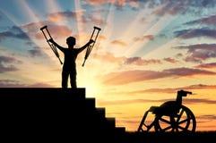 Glücklicher behinderter Junge, der auf sters mit Krücken in seinen Händen und in Rollstuhl steht Stockfotografie