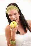 Glücklicher beißender Apfel der jungen Frau Stockfoto