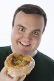 Glücklicher beleibter Mann, der Donut hält Stockfoto