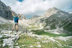 Glücklicher Bergsteiger, der seine Arme vor dem Panorama anhebt Stockfoto