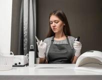 Gl?cklicher Berufmanik?rist der jungen Frau mit Scheren und Nagellack auf grauem Hintergrund stockbilder