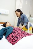 Glücklicher Besuch der kranken Großmutter durch Enkelin Lizenzfreie Stockfotos