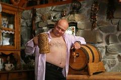 Glücklicher Biergeliebter mit Stein Stockfotografie