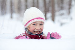Glücklicher Blick des kleinen Mädchens aus Schneewehe heraus Lizenzfreie Stockfotos