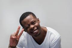 Glücklicher blinzelnder schwarzer Kerl voll der Freude und des Glückes Lizenzfreie Stockfotos