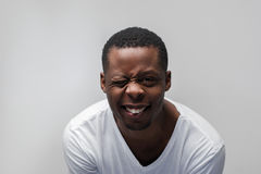 Glücklicher blinzelnder schwarzer Kerl voll der Freude und des Glückes Lizenzfreie Stockfotografie