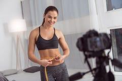 Glücklicher Blogger, der ihre Taille bei der Herstellung eines Videos misst Stockbilder