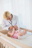 Glücklicher blonder Doktor und Baby, das Stethoskop verwendet Stockfoto