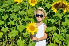 Glücklicher blonder Junge in den Sonnenbrillen und im Hut mit Sonnenblume auf dem Feld, das draußen Kamera betrachtet Stockfotos