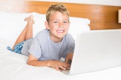 Glücklicher blonder Junge, der auf Bett unter Verwendung des Laptops liegt Lizenzfreies Stockbild