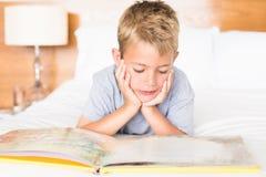 Glücklicher blonder Junge, der auf dem Bett liest ein Märchenbuch liegt Stockfotos
